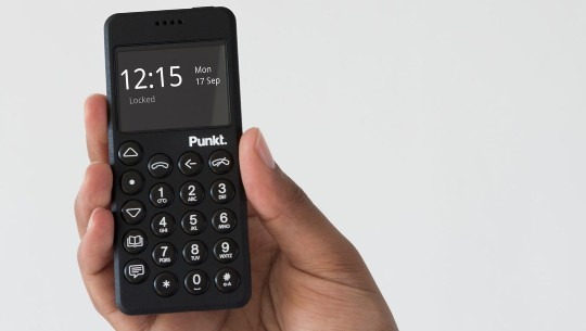 A hand holds a small cellphone with a physical number pad and a compact screen.