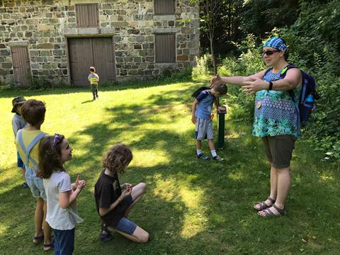 Kelli, standing in front of the stone Tudor Barn, greeting a circle of children with her arms out