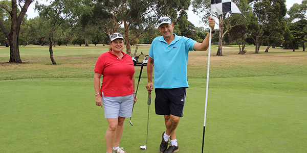 A man and a woman standing on a green at Burnley Golf Course smiling with the man holding the flag