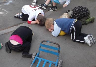 A group of children practise the 'Drop, Cover, Hold' procedure.
