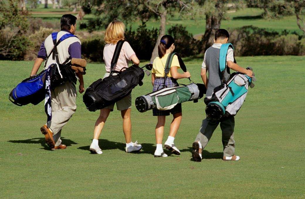 A family of four walk on a golf course holding their golf bags