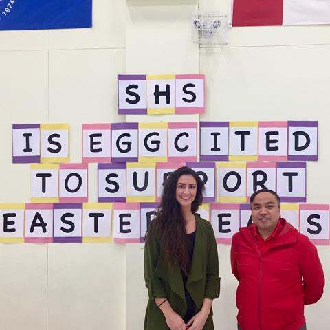 Teacher Roberta Reid and Casey from Easter Seals standing in front of a sign made by students