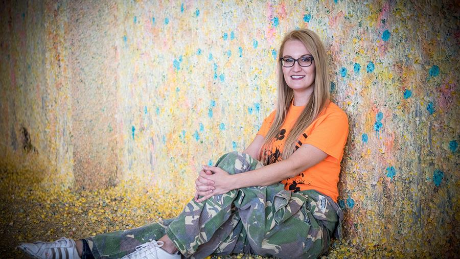 image of Brittany Anderson sitting in front of a wall covered in exploded paint balls