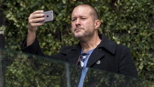 Former Apple design chief Jony Ive holds up an iPhone