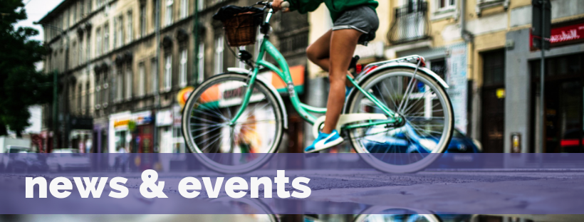 News & Events banner, featuring a photograph of a woman riding a bicycle down a street
