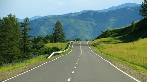 Image of open road and rolling green hills.
