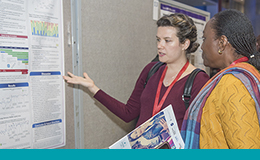 Two people reading a poster at QIPSF 2017