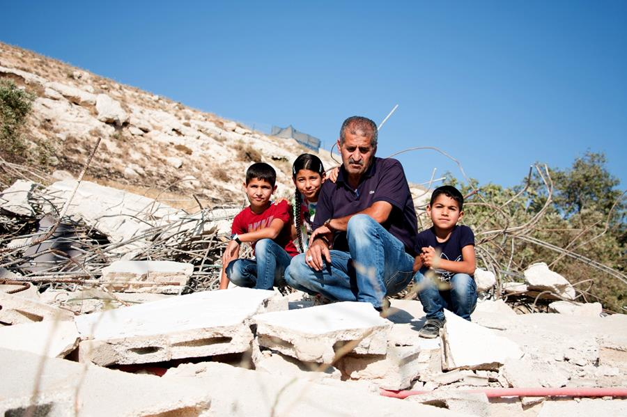 Moussa Abassi with his grandchildren at the remains of the home he built for two of his son's and their families in Silwan, a community just south of Jerusalem's Old City. The home was destroyed by the Israeli government because there was no building permit. The grandchildren are Hanan Abassi, 9, in white, Mohamad Abassi, 7, in red, and Ahmad Abassi, 5, in blue. (MCC Photo/Emily Loewen)