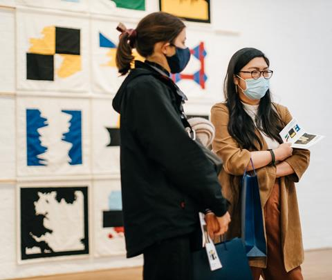 Two young people stand together in front of wall-hung art works. Both wear face masks and have long hair. The art work consists of colourful flags with abstract patterns, made of fabric.