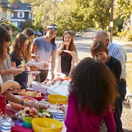 A group of people gather together on a street to eat food together.