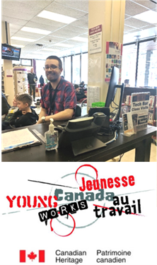 This is a photograph of Jay, the library's new Tech Bar Assistant. He has glasses, brown hairs and is wearing a red and blue plaid shirt while sitting at the Main Library's Tech Bar station. Under his photo, is the red, black and grey logo for Young Canada Works program via Canadian Heritage.