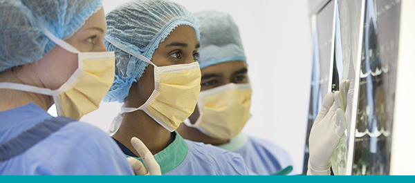 Team of surgeons wearing surgical masks review x-rays