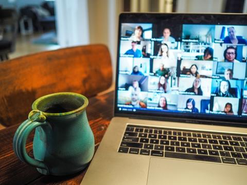 Brown wooden table. On the left is a teal colored coffee mug. On the right is a laptop opened up with the images of several peoples headshots on a virtual meeting like zoom.