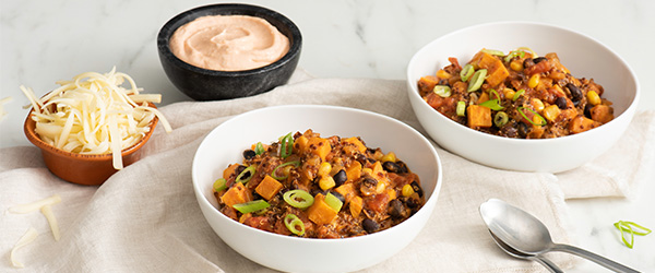 Photo of two bowls of quinoa and sweet potato chili on a white table top with a beige napkin. Cheese and dip in separate bowls on the side.