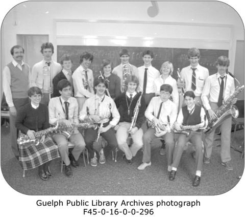 This is a photograph of 16 teens holding their instruments. There are two rows of students who are part of their Highschool Stage band.