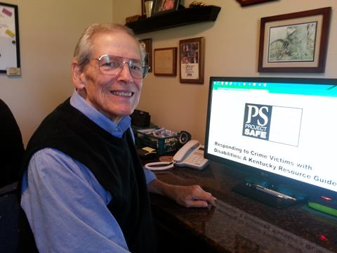 Older man smiling at the camera while working on a computer