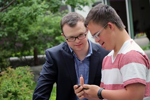 Two men with Down syndrome looking at a smart phone.