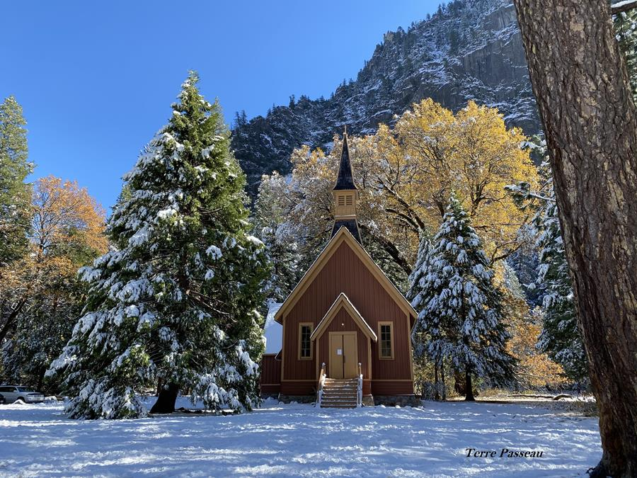 Landscape shot of the quaint Yosemite Valley Chapel in winter, with a thin layer of fresh snow covering the granite wall behind it, the trees surrounding it, and the wintry meadow in front.