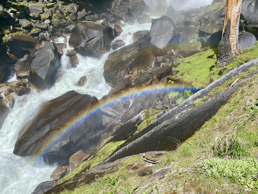 Close-up shot of a rainbow visible in the rocky spray zone around a roaring Merced River - a common sight for hikers on the Mist Trail in Yosemite.