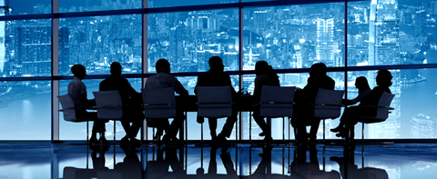 Silhouettes of people at a meeting table in front of a evening city lights scene