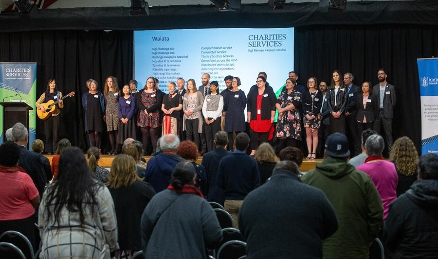 Charities Services team stand on stage at the 2020 Annual Meeting performing a waiata to a crowd of people.