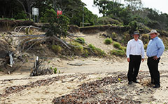 Officers standing near beach erosion