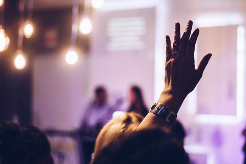 Person raising hand at conference