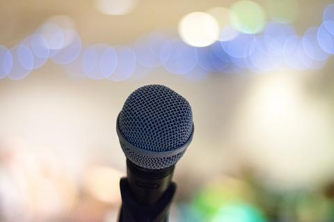 Selective focus photo of a microphone in front of a brightly lit crowd