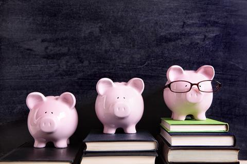 Three piggy banks in front of chalkboard