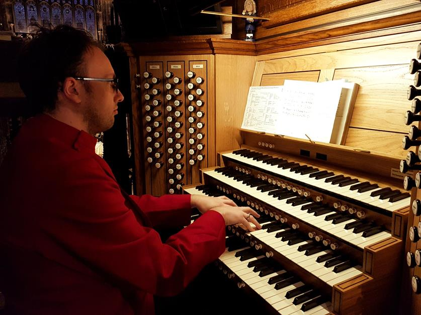A male dressed in a red robe playing the Cathedral organ