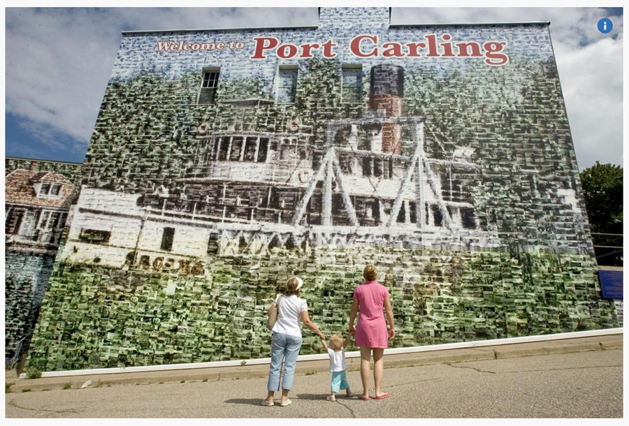 Picture of two women and a baby in front of the Port Carling mural