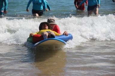 Child with disability lying on a surfboard catches a wave with help from a volunteer