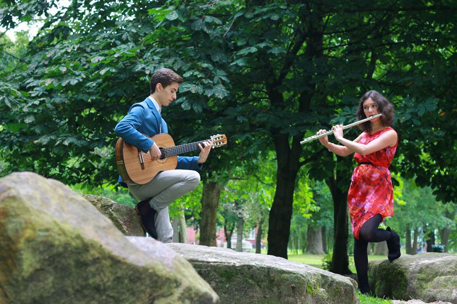 Man playing the guitar, women playing the flute standing on rocks with trees in the background