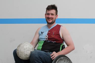 Man in a wheelchair holding a rugby ball