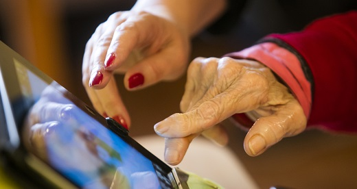 Hands of worker and older person using tablet computer