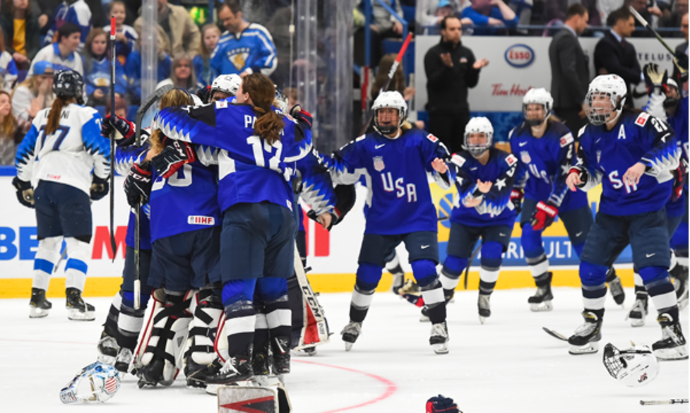 Team USA hockey players huddle on ice in celebration