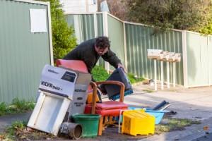 Man placing hard waste on kerb