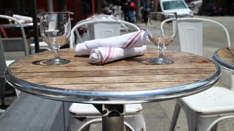A table with glasses on it ready for outdoor dining.