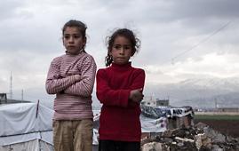 Two girls standing in refugee settlement near Syrian border
