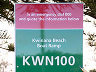 A Beach Emergency Number sign installed on a beachfront