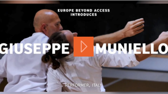 Two men in white shirts dance together, Giuseppe with long dark hair tied up