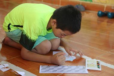A boy sits on the floor drawing