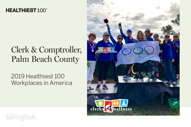 Healthiest 100 award designation with group photo of Clerk amd clerk employees standing on Clerks' Olympics outdoor stage
