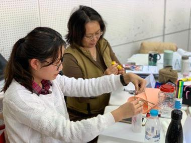 Two teachers sit making props for their drama classes
