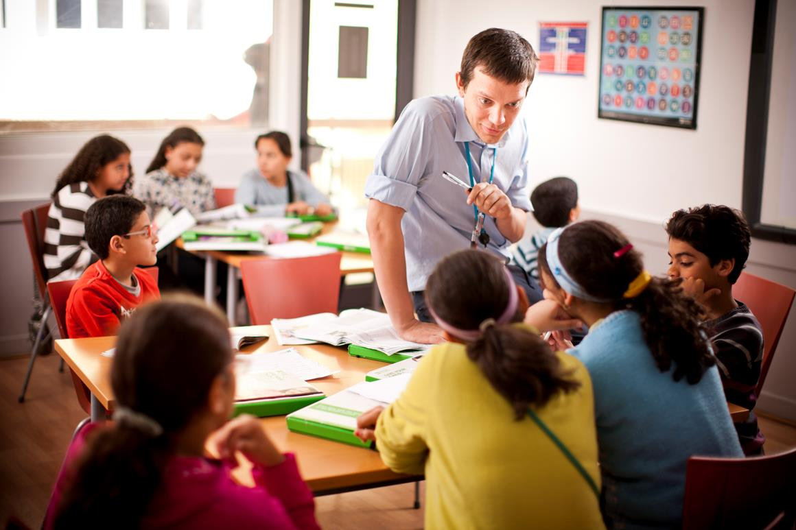 A male teacher in a class talking to children who are sitting in teams.