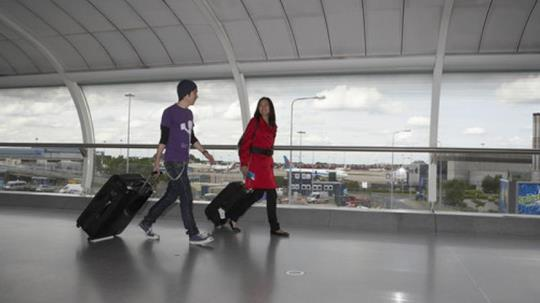 A boy and a girl at an airport terminal carrying their bag