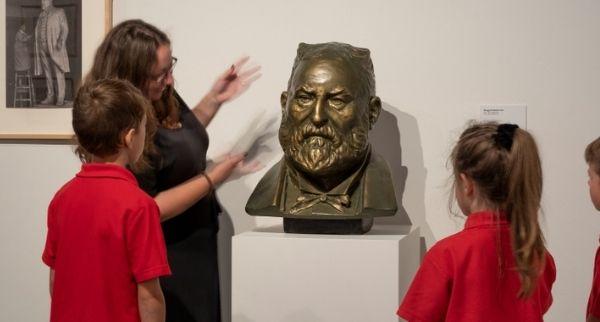 Lady showing kids brass head in gallery