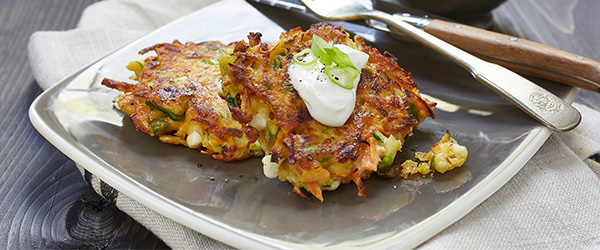 Photo of vegetable pancakes with dollop of sour cream.