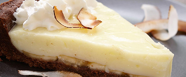 Photo of a slice of pie with chocolate crust, layer of bananas, layer of vanilla custard and topped with coconut and whipped cream.
