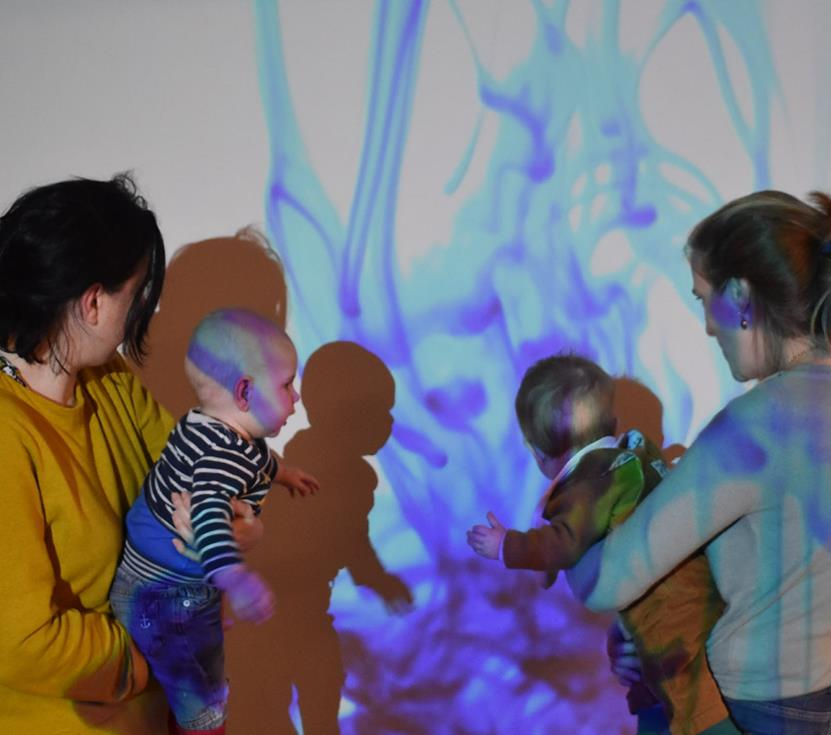 Image description: The back of two young people carrying babies create shadows on a white wall. On the white wall there is a light projection of swirling blue ink in water.